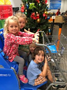 [image description: four young smiling children squashed into a grocery cart in front of a holiday store display.]